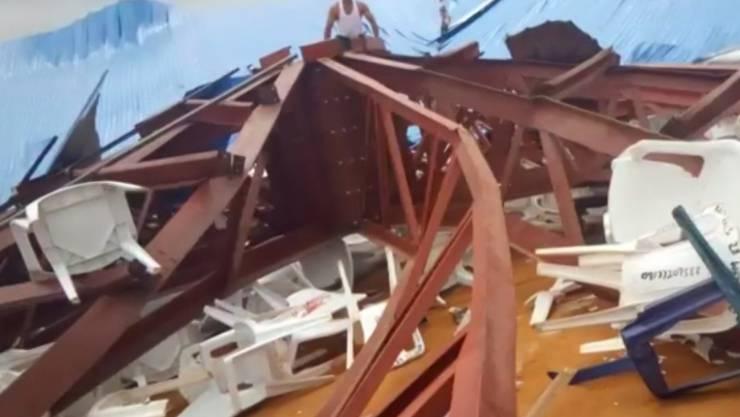 Einheimische nehmen eine eingestürzte Kirche in Uyo in Nigeria in Augenschein. Das Dach aus Metall war während eines Gottesdiensts über den Teilnehmern eingestürzt. Viele Menschen kamen dabei ums Leben.