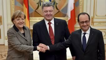 Bundeskanzlerin Merkel will sich in Berlin mit dem ukrainischen Staatschef Poroschenko (Mitte) sowie Frankreichs Präsidenten Hollande treffen. Hier ein Dreiertreffen in Kiew. (Archiv)