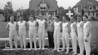 Die Schweizer Nationalmannschaft der Kunstturner im Jahre 1936 mit August Güttinger (in Zivil) und Georges Miez (links von Güttinger)