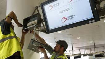 Arbeiter reparieren einen Bildschirm in der Abflughalle des Brüsseler Flughafens Zaventem. Ein Teil der Abflughalle soll am Sonntag wieder in Betrieb gehen.