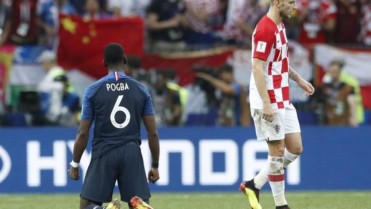 Während Frankreichs Paul Pogba beim Abpfiff des WM-Finals erleichtert in die Knie geht, verlässt der Kroate Ivan Rakitic (rechts) enttäuscht den Platz