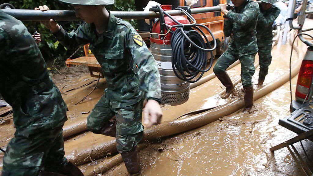 Suchmannschaften pumpen mit schweren Geräten Wasser aus der Höhle ab.