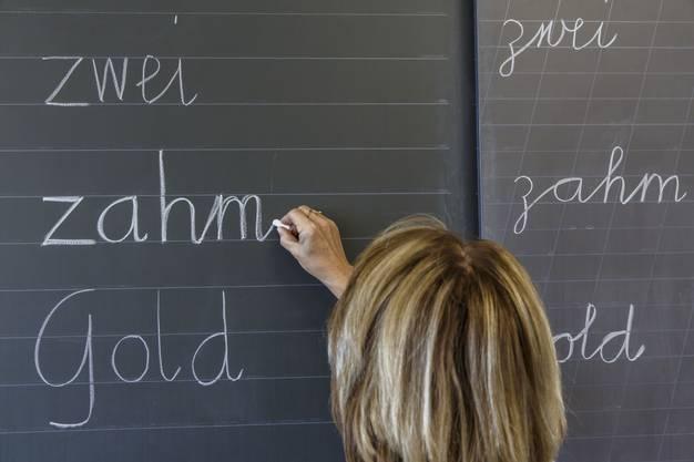 Ruth Schilt, Primarschullehrerin in Grenchen, schreibt in Basisschrift an die Wandtafel