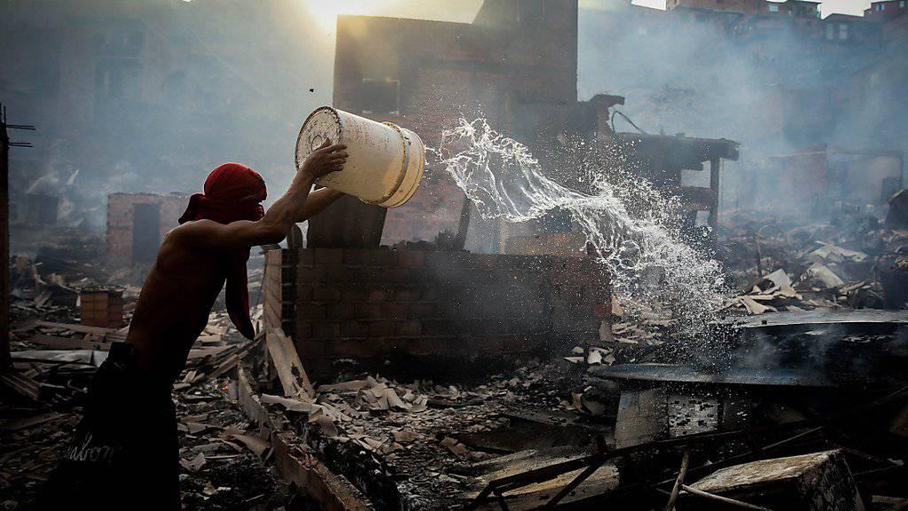 Mit blossen Händen gegen die Feuersbrunst: Ein Bewohner des Elendsviertels Paraisópolis in São Paulo versucht die Flammen zu löschen.