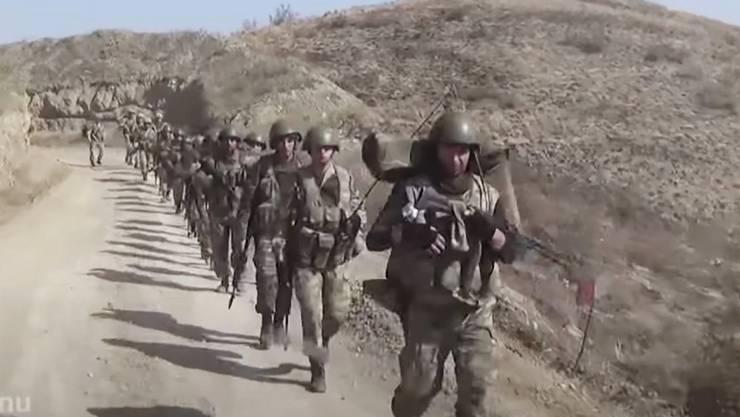 Aserbaidschanische Soldaten marschieren in der Konfliktregion Bergkarabach. Die von Russland ausgehandelte Waffenruhe ist brüchig.