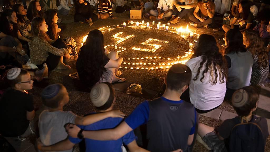 ARCHIV - Menschen sitzen während einer Mahnwache um einen Kreis von Kerzen zum Gedenken an die 45 Opfer, die bei einer Massenpanik an einem Wallfahrtsort ums Leben gekommen sind. Nach der Polizei will auch der sogenannte Staatskontrolleur in Israel das Unglück mit Dutzenden Toten in einem Wallfahrtsort im Norden des Landes untersuchen. Foto: Oded Balilty/AP/dpa