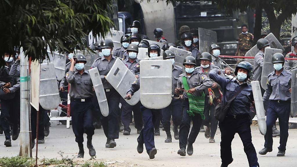 Polizisten stürmen auf Demonstranten in Mandalay zu, um sie zu vertreiben. Foto: --/AP/dpa