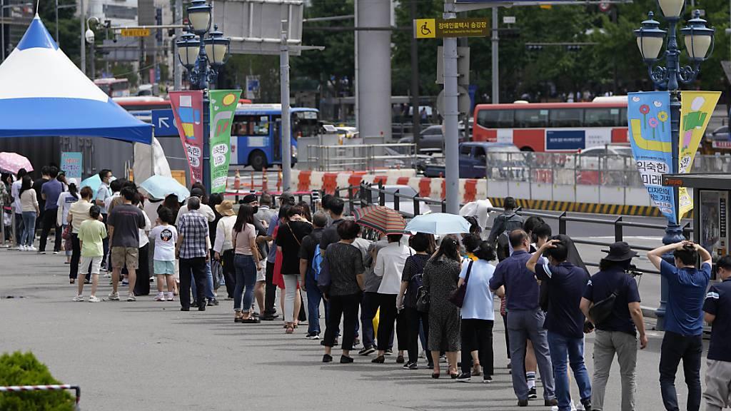Menschen stehen Schlange vor einem Corona-Testzentrum. Südkorea hat den zweithöchsten Tageswert registrierter Corona-Neuinfektionen seit Beginn der Pandemie verzeichnet. Foto: Lee Jin-Man/AP/dpa Foto: Lee Jin-Man/AP/dpa