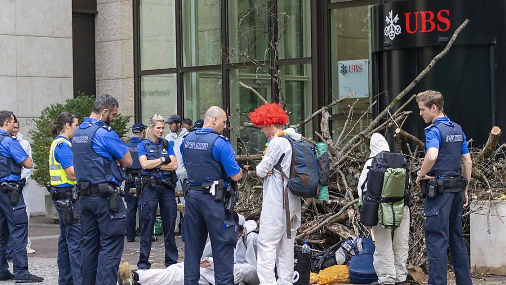Polizisten räumten am Montag die Blockade der Aktivisten einer Gruppe namens «Collective Climate Justice» vor dem UBS-Bürogebäude am Aeschenplatz in Basel. Im Hintergrund eine Holzbeige, die an Schwemmholz erinnert, als Sperre vor der Türe. (Archivbild)