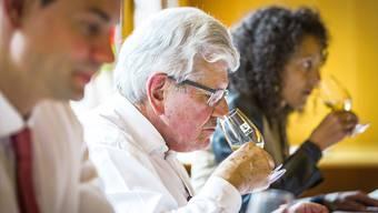 Als Jurypräsident und Erfinder der Staatswein-Kürung prüft Roland Brogli konzentriert einen Weisswein. Chris Iseli