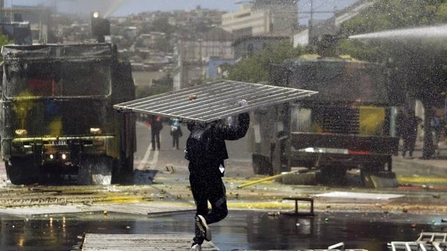 Ein Demonstrant in der chilenischen Stadt Valparaiso geht mit einem Barrikadenteil auf die Wasserwerfer zu