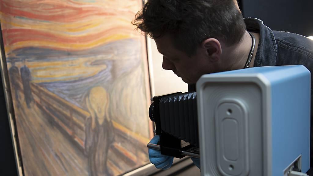 Ein Mann richtet eine Infrarotkamera auf das Gemälde «Der Schrei» von Edvard Munch.