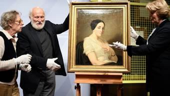 """Die deutsche Kulturstaatsministerin Monika Grütters (r) gibt das im Gurlitt-Nachlass gefundene Bild """"Portrait de jeune femme assise"""" von Thomas Couture an die Nachkommen des rechtmässigen Besitzers zurück."""
