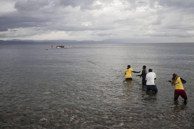 Helfer ziehen die Boote durch die Brandung an den Strand
