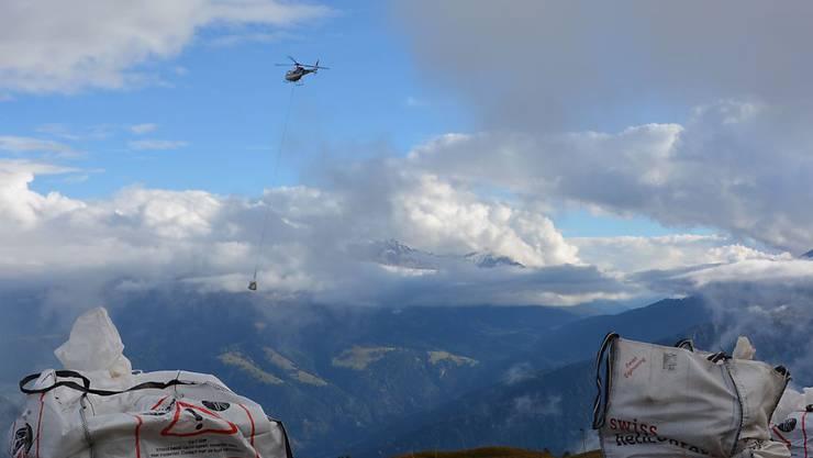 Ein Helikopter transportiert die Grasplatten für ein Experiment über Alpenpflanzen am Calanda.