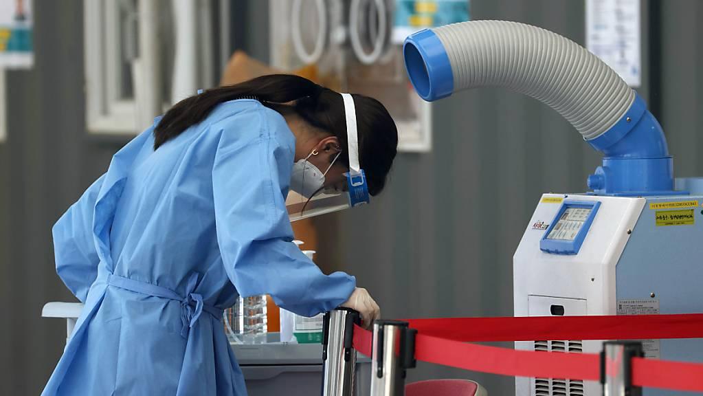 Eine medizinische Mitarbeiterin einer Corona-Teststation steht in Seoul vor einem Luftkühler. Zuletzt wurden im Land 826 neue Infektionen gemeldet, der höchste Wert seit fast sechs Monaten.