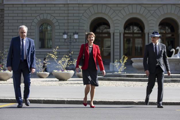 Bundesrat Alain Berset mit Hut und Bundespräsidentin Simonetta Sommaruga sowie Bundesrat Guy Parmelin (v.r.) auf dem Weg zu einer Medienkonferenz.