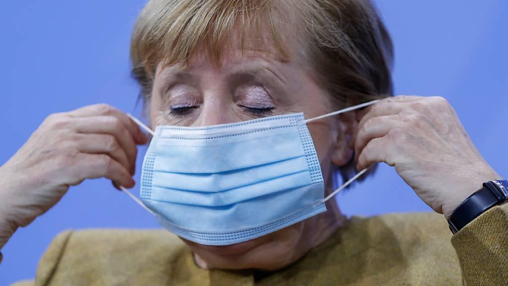 Bundeskanzlerin Angela Merkel (CDU) setzt ihre Gesichtsmaske nach ihrer Pressekonferenz auf.
