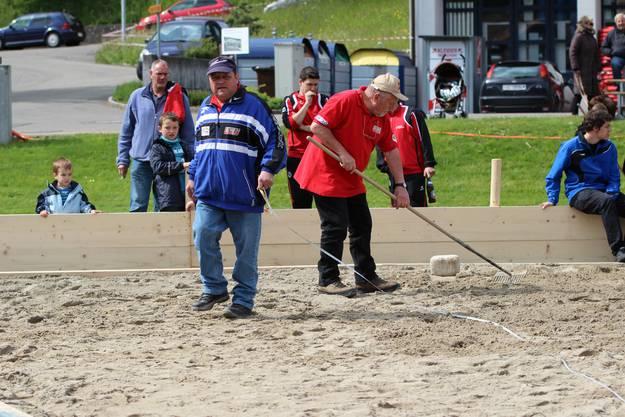 Nach jedem Wurf wird der Sandplatz mit dem Rechen bearbeitet