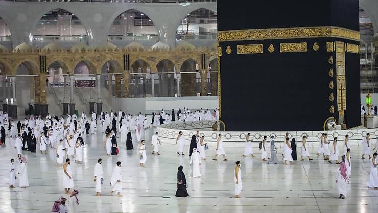 HANDOUT - Muslime beten um die Kaaba, das kubische Gebäude in der Großen Moschee, während des ersten Tages der Umrah in der muslimischen heiligen Stadt Mekka. Foto: Saudi Ministry of Hajj and Umrah/AP/dpa - ACHTUNG: Nur zur redaktionellen Verwendung und nur mit vollständiger Nennung des vorstehenden Credits