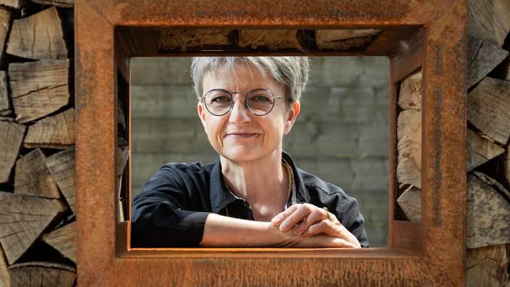 Fürs Foto lächelt Maya Bally durch eine kleine Öffnung im grossen Holzstapel, der in ihrem Garten steht.