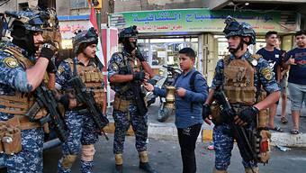 Ein Strassenverkäufer im Stadtteil Sadr City von Bagdad verkauft der Polizei Kaffee. Iraks Regierungschef Adel Abdel Mahdi hatte am Montag die Armee aus dem Stadtteil abgezogen und sie durch Polizisten ersetzt.