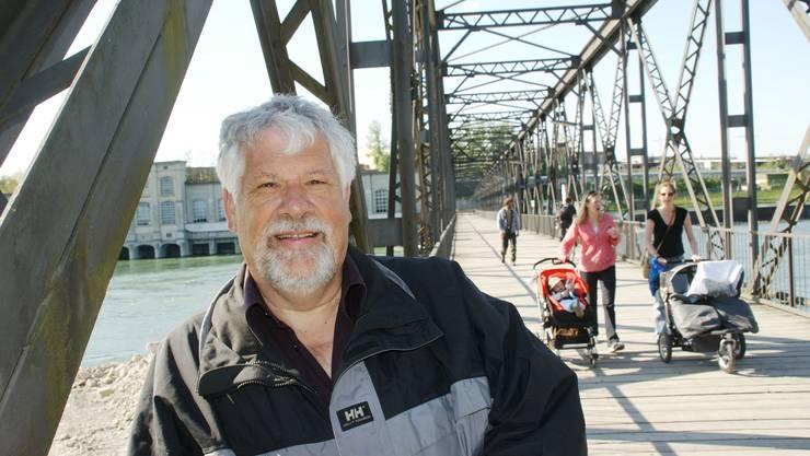 Peter Scholer auf dem Eisensteg über den Rhein; hinter ihm das alte Maschinenhaus des Kraftwerks Rheinfelden.