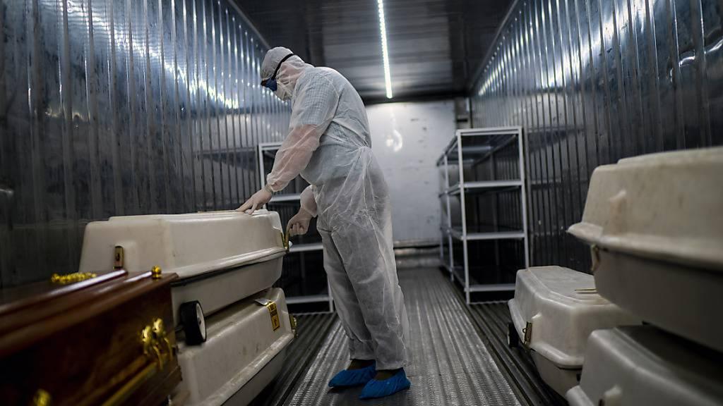 ARCHIV - Ein Angestellter einer Leichenhalle im südafrikanischen Johannesburg trägt Schutzkleidung und überprüft in einem Kühlcontainer Särge mit Corona-Opfern. Foto: Jerome Delay/AP/dpa