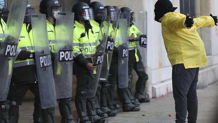 Ein Demonstrant steht während eines Protests gegen die Regierung vor Polizisten. Foto: Fernando Vergara/AP/dpa