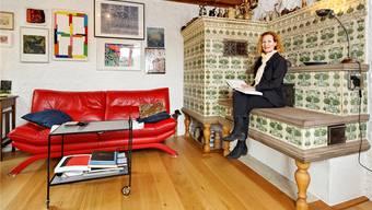 Kleine Pause zwischen den Auftritten: Brigitta Luisa Merki auf der «Chouscht» des Kachelofens im Wohnzimmer ihres Bauernhauses.ANDRé ALBRECHT