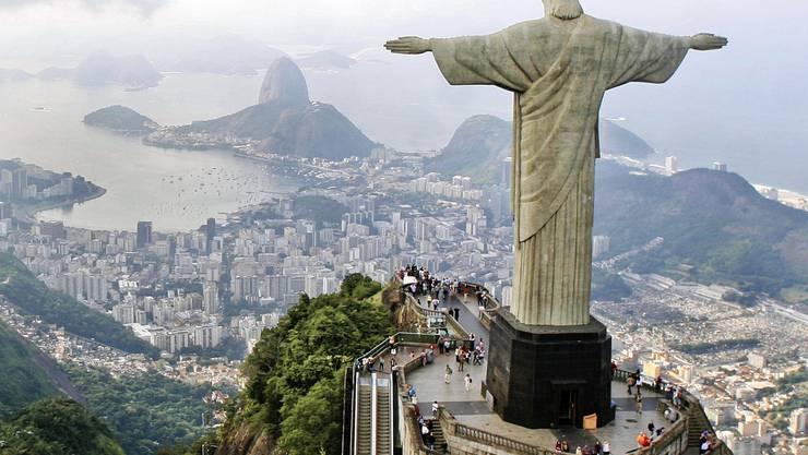 Die 30 Meter hohe Statue Cristo Redentor blickt auf die brasilianische Stadt Rio de Janeiro und den Zuckerhut hinunter. Beides sind beliebte Reiseziele für Touristen.