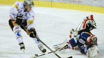 Biels Goalie Simon Rytz im Kampf um den Puck gegen Zugs Alessio Bertaggia.