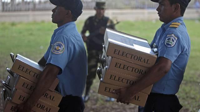 Polizisten bringen die Wahlzettel in die Wahllokahle