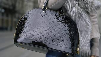 Der Luxusgüterkonzern LVMH machte im vergangenen Quartal mehr Umsatz - zum Konzern gehört auch die Marke Louis Vuitton, von der diese Frau eine Tasche trägt. (Symbolbild)