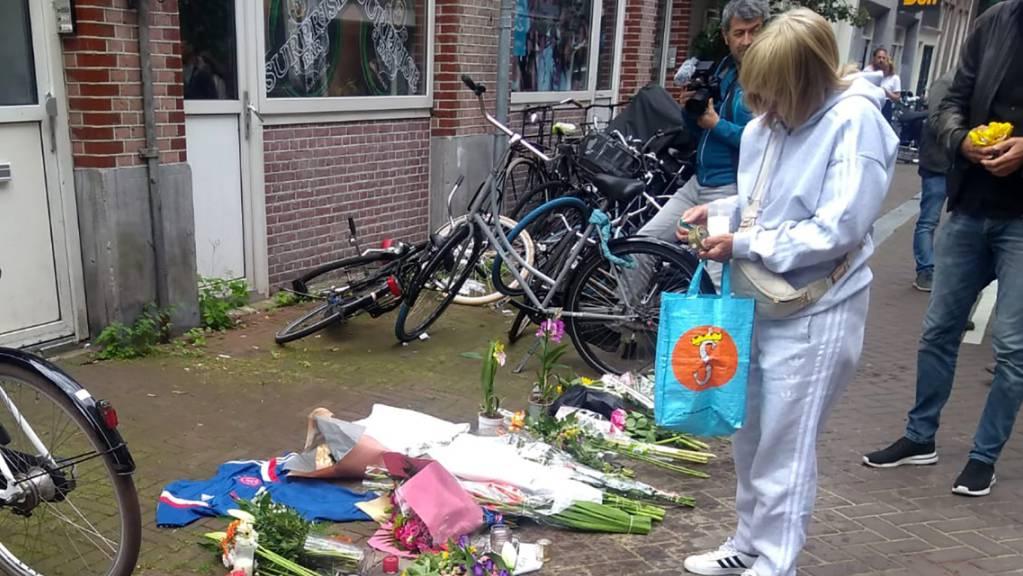 Eine Frau steht vor Blumen am Tatort, nachdem dort am Abend des 6. Juli der niederländische Journalist de Vries niedergeschossen wurde.