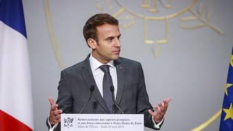 Die Umfragewerte von Emmanuel Macron - im Bild beim Dank an die Feuerwehrleute - sind seit dem verheerenden Brand in der Pariser Kathedrale Notre-Dame leicht gestiegen. (Archivbild)