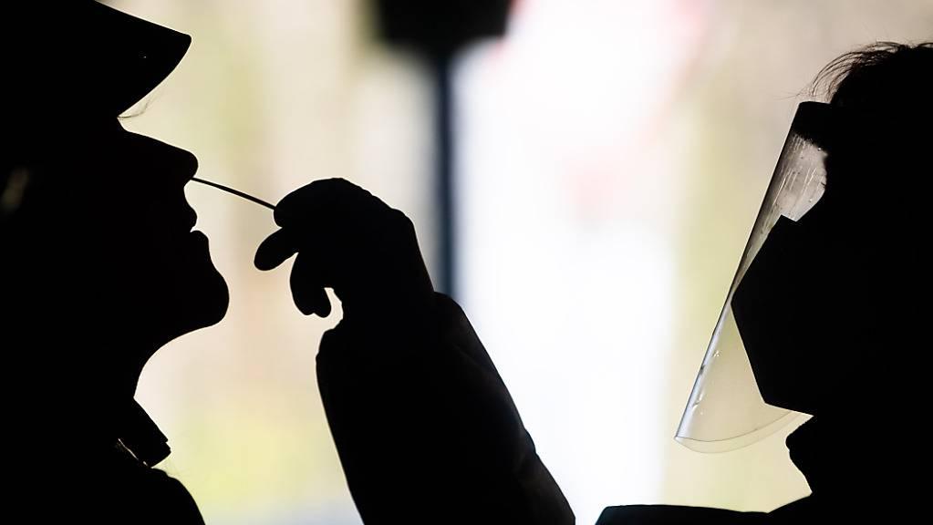 Bei einem Mann wird ein Corona-Test in einem Schnelltest-Zentrum in Hannover genommen. (Archiv)