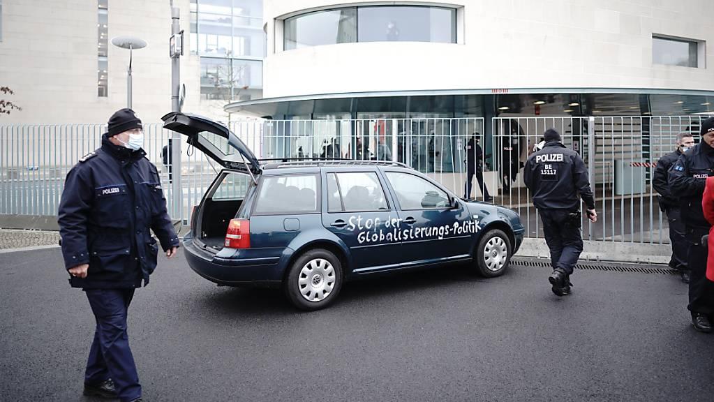 Ein Auto steht vor dem Tor des Bundeskanzleramts. Auf der Tür ist die Aufschrift «Stop der Globalisierungs-Politik» zu lesen.