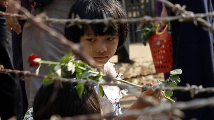 Ein Mädchen, das vor dem berüchtigten Insein-Gefängnis von Rangun auf die Freilassung eines Verwandten wartet, hält eine Rose in der Hand. Seit dem Amtsantritt der neuen Regierung in Myanmar wurden laut der Polizei knapp 200 politische Aktivisten freigelassen.