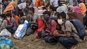Geflüchtete Rohingya sitzen am Strand der Provinz Lancok, nachdem sie mit einem Boot dort angekommen sind. Indonesische Fischer entdeckten die hungernden und geschwächten Rohingya-Muslime auf dem Holzboot, das vor Indonesiens nördlichster Provinz Aceh trieb. Foto: Zik Maulana/AP/dpa