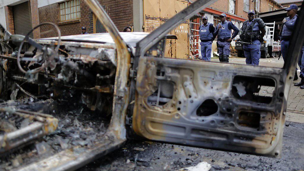Polizisten sichern nach Ausschreitungen eine Strasse in Johannesburg. Zahlreiche Geschäfte von Einwanderern wurden geplündert, grosse Schäden angerichtet.