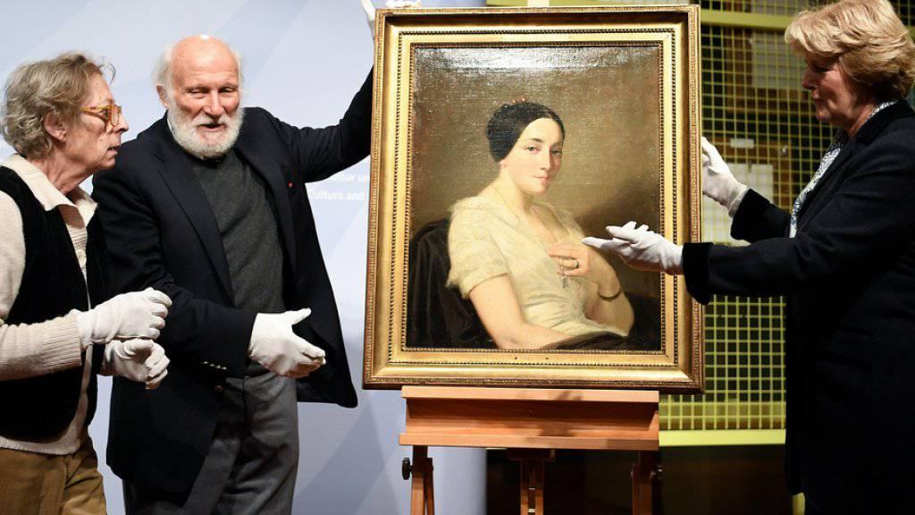 Die deutsche Kulturstaatsministerin Monika Grütters (r) gibt das im Gurlitt-Nachlass gefundene Bild «Portrait de jeune femme assise» von Thomas Couture an die Nachkommen des rechtmässigen Besitzers zurück.