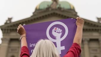 Eine Frau schwingt die Fahne des Frauenstreiks vor dem Bundeshaus. (Symbolbild)