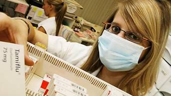 Apothekerin holt Tamiflu-Packung aus der Schublade (Archiv)