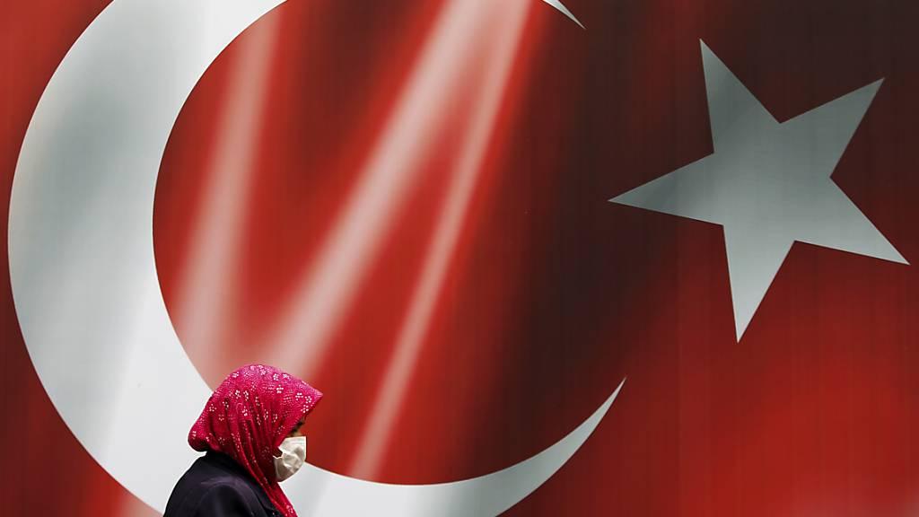 ARCHIV - Eine Frau, die eine Maske trägt, geht in Istanbul an einer türkischen Flagge vorbei.(Symbolbild) Foto: Emrah Gurel/AP/dpa