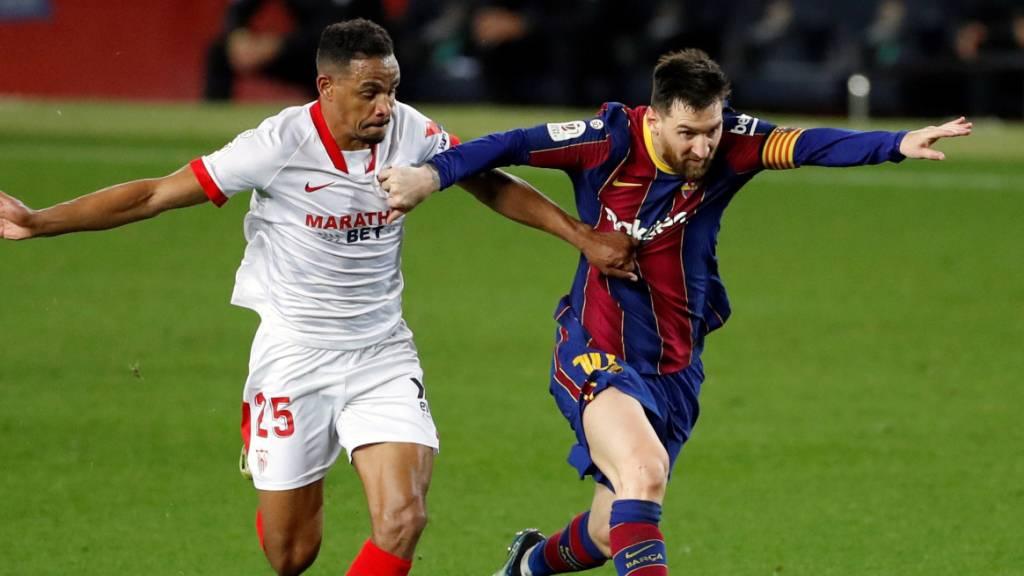 Lionel Messi (rechts) muss sich hier gegen Sevillas Fernando Reges wehren