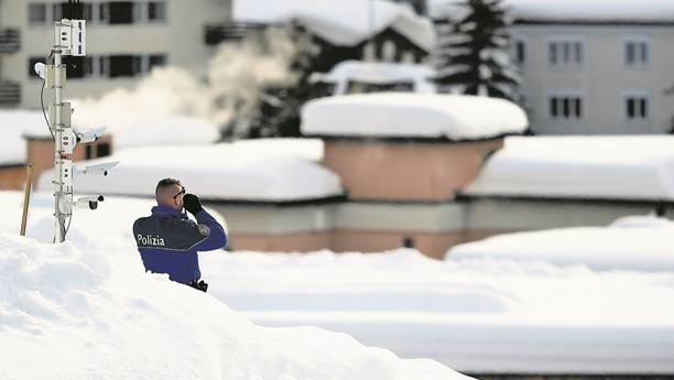 Ein Polizist bewacht das WEF in Davos von einem Dach aus.