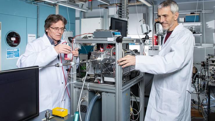 Urs Baltensperger (l.) und André Prévôt (r.) am neu entwickelten Gerät das Moleküle in Feinstaub analysiert.