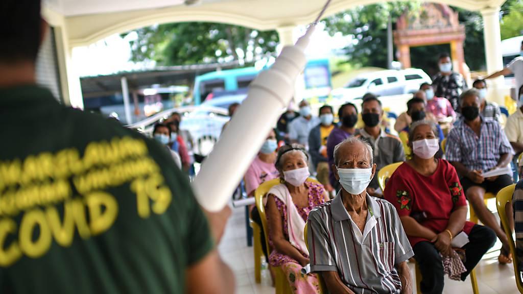 Eine Corona-Informationsveranstaltung im Bezirk Padang Terap in Malaysia über den Schutz vor dem Coronavirus und über die Impfung. Foto: Adib Hasri/BERNAMA/dpa
