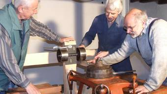 Fachwissen und Herzblut: Die Zimmermänner Günter Werren und Toni Amrein montieren mit Mechaniker Jacques Linsi (von links) eine Umlenkrolle für den Antrieb des «Plansichters», der verschieden feines Mehl aussiebt. (Bild Thomas Stöckli)